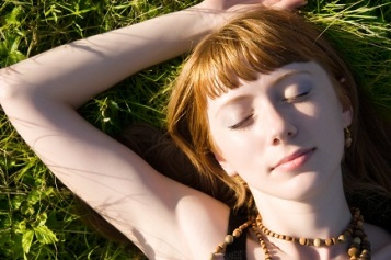 Young woman sleeping on a green grass